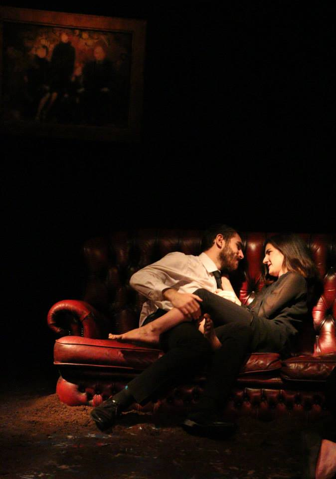 Photo of two characters cuddling on a sofa in the play Victory.
